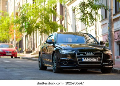 Kiev, Ukraine - October 15, 2017: Modern new cars parked on the side of the street in a city. Shiny vehicle parked by the curb. Urban transportation infrastructure.
