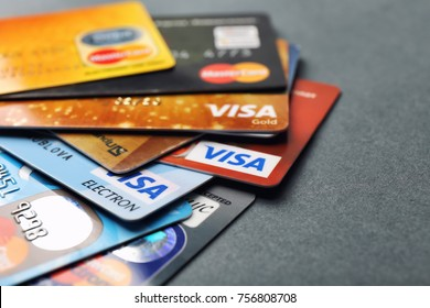 KIEV, UKRAINE - OCTOBER 2, 2017: Different Visa and MasterCard credit cards on grey background