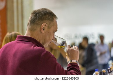 KIEV, UKRAINE - OCTOBER 20, 2018: Unrecognized middle aged man tastes whisky at 4th Ukrainian Whisky Dram Festival organized by Good Wine company in Artistic Arsenal.
