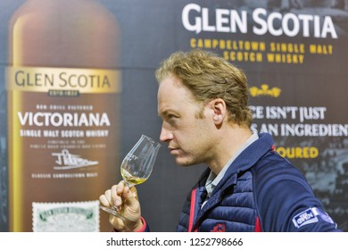 KIEV, UKRAINE - OCTOBER 20, 2018: Man tasting Glen Scotia Scotch highland single malt whisky at booth of 4th Ukrainian Whisky Dram Festival organized by Good Wine company in Artistic Arsenal.