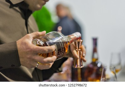 KIEV, UKRAINE - OCTOBER 20, 2018: Man sommelier pours Woodford bourbon whisky at booth of 4th Ukrainian Whisky Dram Festival organized by Good Wine company in Artistic Arsenal.