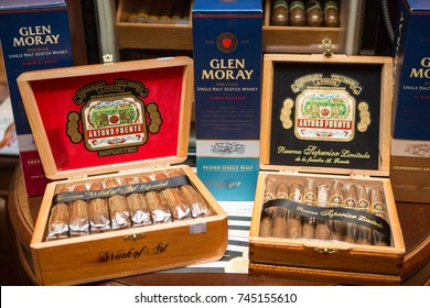 Kiev, Ukraine October 24, 2017: An expensive wooden box with great Dominicana cigars and box with alcohol. Close up. eft last cigar on brown wooden box