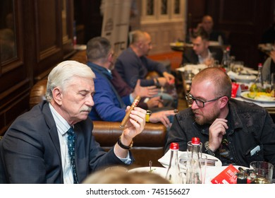 Kiev, Ukraine October 24, 2017: Elegantly dressed men smoking cigars in  luxurious cigar club during cigar party, drink alcohol
