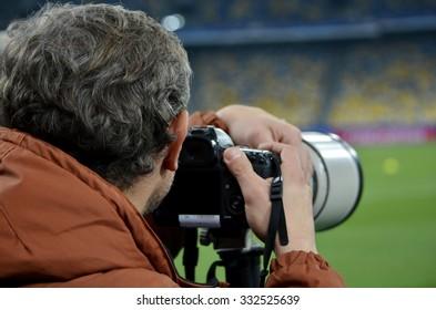 KIEV, UKRAINE - OKT 20: Photojournalist with a camera during the UEFA Champions League match between Dinamo Kiev vs Chelsea (London, England), 20 October 2015, Olympic NSC, Ukraine
