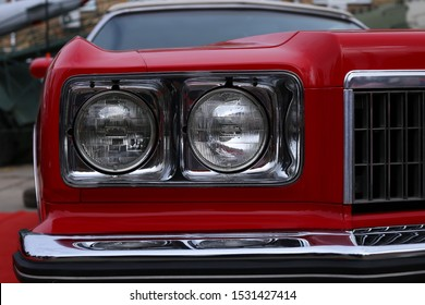 Kiev, Ukraine, on October 5, 2019. Two round headlights in a rectangular chrome frame of the American car Chevrolet Impala 1975 red.