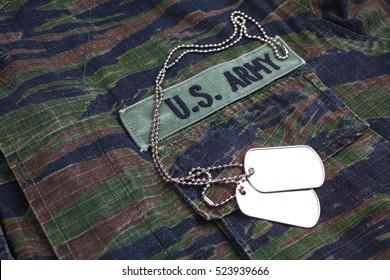 KIEV, UKRAINE - Sept 12, 2016. US ARMY branch tape and dog tags on tiger stripe camouflage uniform