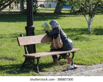 Kiev, Ukraine - September 11, 2015: Woman parishioner reading a book in the courtyard of an Orthodox church