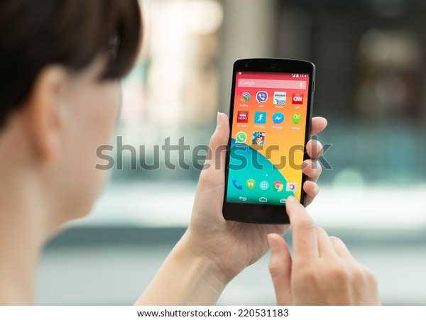 Kiev, Ukraine - September 14, 2014: Woman using a brand new Google Nexus 5 outdoors. Google Nexus 5 is powered by Android 4.4 version, manufactured by LG Electronics.