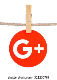 KIEV, UKRAINE - SEPTEMBER 16, 2015: Popular social media Google plus hanging on the clothesline isolated on white background.Google plus which provides the ability to communicate via the Internet.