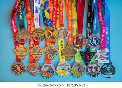 Kiev, Ukraine. September 2 2018 Many different sports medals on a blue background. Medals for half marathon, marathon and other distances