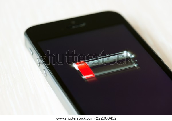 Kiev, Ukraine - September 22, 2014: The brand new Apple iPhone 5S lying on a desk with low battery symbol on a screen. Developed by Apple inc. and was released on September 20, 2013.