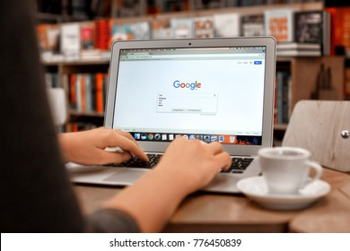 KIEV, UKRAINE - SEPTEMBER 25, 2017: Young woman using Apple MacBook Air with Google search page on screen at table