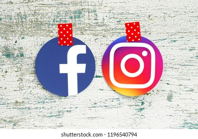 Kiev, Ukraine - September 27, 2018: Facebook and Instagram round icons printed on paper and taped with red in white dots adhesive tape on old wood