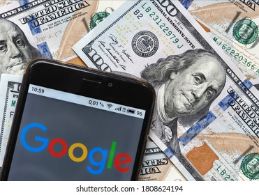 Kiev, Ukraine, September 4, 2020. Editorial illustrative. In this photo a Google logo is seen displayed on a smartphone lying on 100 dollar bills