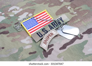 KIEV, UKRAINE - September 5, 2015. US ARMY sniper tab, flag patch,  with dog tag on camouflage uniform