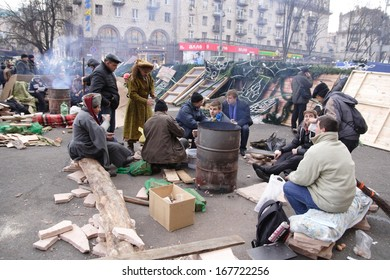 KIEV, UKRAINE-DECEMBER 5, 2013: Barricade at the Independence Square in Kiev. Protesters are heated by the fire.