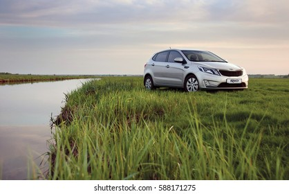 KIEV, UKRAINE-JULY 4, 2016: Kia Rio parked on the field near the river.  Automotive photography. Space for text. Nature background with car. Landscape with car. Spring field and car.