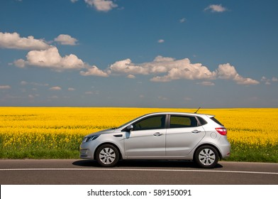 KIEV, UKRAINE-JULY 4, 2016: Kia Rio parked on the road near the field.  Automotive photography. Space for text. Nature background with car. Landscape with car. Spring field and car.