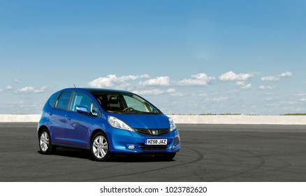 KIEV, UKRAINE-JULY 4,2017: Blue car Honda Jazz parked on the road against the background of the sunny sky. Automotive photography. Space for text. Background with car.
