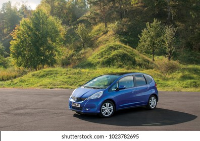 KIEV, UKRAINE-JULY 4,2017: Blue car Honda Jazz parked on the road against the background of the forest. Automotive photography. Space for text. Background with car.
