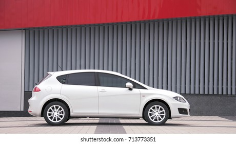 KIEV, UKRAINE-JULY 4,2017: White car parked on a city street. Automotive photography. Space for text. Urban background with car. Cityscape with car. Wall and car.