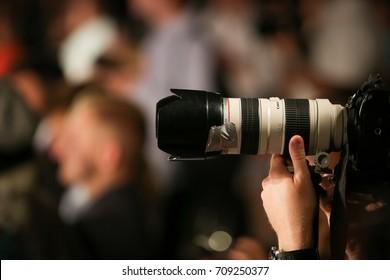 KIEV, UKRAINE-September 4, 2017: Paparazzi photographer in the crowd. Canon 70-200mm L Lens. A detective or paparazzi secretly takes photos.