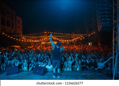 KIEV-11 AUGUST,2018: Famous white rap singer Ligalize performing live set on stage of summer music festival Kurazh.Hip hop performer singing in open air night club.View from stage on concert crowd