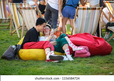 KIEV-11 AUGUST,2018: Group of people on lounge chairs relaxing at summer festival Kurazh. Happy young couple chilling with smart phones in loung zone at entertainment event