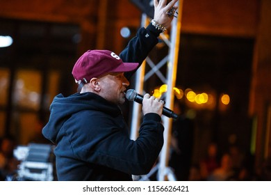 KIEV-11 AUGUST,2018: Rap singer Ligalize singing in microphone on stage of Kurazh summer music festival in open air night club.White rapper with tattoos sings in mic on scene.Hip hop star performance