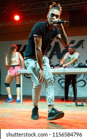 KIEV-11 AUGUST,2018: Young black rap singer,back mc of XL Deluxe with microphone in hand performing live set on stage in nightclub Kurazh.Hip hop concert performer with mic on scene in the club
