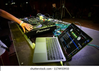 KIEV-11 JULY,2018: Female DJ plays music with Traktor DJ software installed on Apple Macbook Pro at summer festival Bazar.Professional disc jockey audio equipment at work