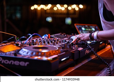 KIEV-11 JULY,2018: Female dj plays concert set with CD player turn table and Pioneer four channel sound mixer device.DJ Senorita playing tracks on summer festival in night club.Hip hop music party mix