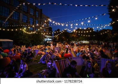 KIEV-11 JULY,2018: Group of young people chilling in lounge chairs on summer festival Bazar