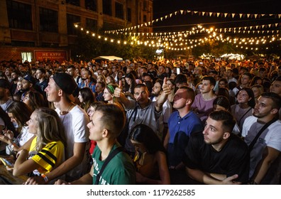 KIEV-11 JULY,2018: Happy music fans on rap concert near the stage at summer festival Bazar.Cheerful young man show thumbs up.Entertainment event audience listening to famous musician on scene