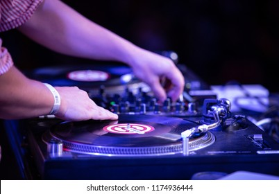 KIEV-11 JULY,2018: Hip hop dj scratches vinyl records with retro Technics SL 1210 turn table player on summer music festival Bazar. Professional disc jockey audio equipment on concert stage