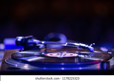 KIEV-11 JULY,2018: Retro Technics SL 1210 turntable player with old analog vinyl record on stage in night club.Professional club dj setup for playing techno music.Scratch tracks with turn table