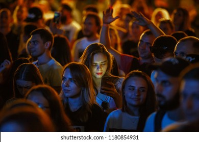 KIEV-11 JULY,2018: Student girl using smartphone on dance floor at summer music festival Bazar. Young woman uses modern mobile phone in big crowd on concert