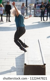 KIEV-24 JUNE,2018: Young white girl grinds rail box with aggressive inline skates on skate contest in outdoor skatepark.Extreme sports background.Cool youth lifestyle.Female athlete rides on blades