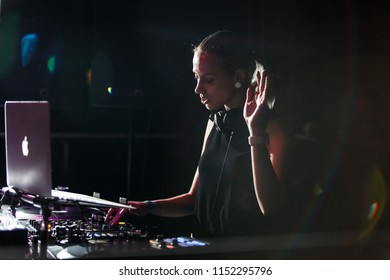 KIEV-4 JULY,2018: Club party dj plays live music set on stage in night club.Young blonde female disc jockey Lime Kid playing musical tracks on drum and bass festival in the club