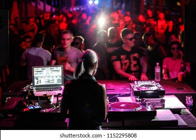 KIEV-4 JULY,2018: Club party dj plays edm music set on stage in night club.Young blonde female disc jockey playing musical tracks on drum and bass festival in the club.Rave party background