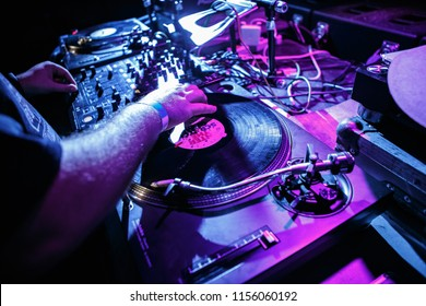 KIEV-4 JULY,2018: Dj Panchez scratches vinyl records on retro Technics SL turntable player device in night club on party.Overhead view of djs turn tables at concert stage in blue and magenta lights
