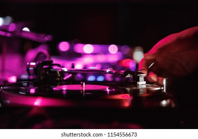 KIEV-4 JULY,2018: Dj put needle on vinyl record at party.Retro Technics SL-1210 turntables and Shure M44-7 spherical needle in disc jockey setup.Professional djs audio equipment on stage in night club