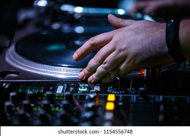 KIEV-4 JULY,2018: Hip hop dj scratches vinyl records with Technics SL-1210 turntables.Professional disc jockey audio equipment on concert stage in night club.Djs setup for techno music party