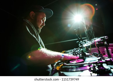 KIEV-4 JULY,2018: Party dj mixes music tracks and scratch vinyl records on vintage Technics SL-1210 turn table player.Dj Panchez plays set in stage in nightclub.Drum and bass summer festival in club