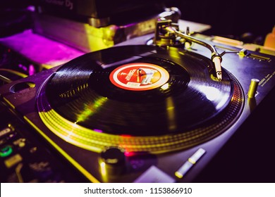 KIEV-4 JULY,2018: Retro DJ turntable plays vinyl disc with music on party in music hall. Professional Technics SL-1210 turn table player with spherical Shure M44 needle playing analog record on party