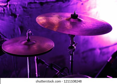 KIEV-9 SEPTEMBER,2018: Professional drum kit cymbals on stage in bright magenta lights.Music hall audio equipment for rock concert.Drumset for drummer musician on nigthclub Party Bar scene