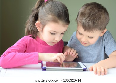 Kiev/Ukraine - 02.26.2019 White caucasian toddler boy and beautiful girl playing together on tablet games. Portrait of smiling little brother and sister. Children play game and drawing on iPad tablet