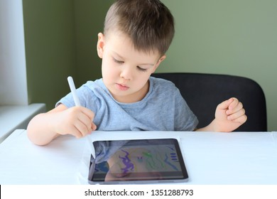 Kiev/Ukraine - 02.26.2019 White cute smiling toddler boy drawing on the screen of iPad Pro with apple pencil. Boy playing game on iPad. Portrait of happiness caucasian little boy with IPad tablet.