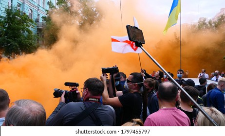 Kiev/Ukraine - 08.13.2020: photo journalists reporters shooting with their cameras at cloud of thick yellow smoke at street protest action against president Lukashenko near belarusian Embassy in Kyiv.
