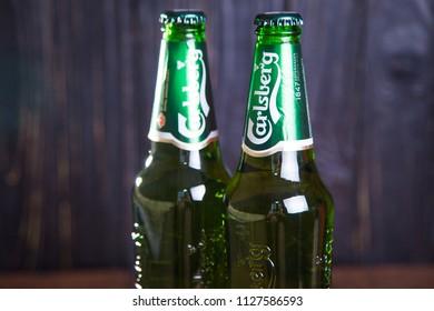 Kiev,Ukraine - July 05, 2018: Bottle Of Carlsberg beer on wooden background. Danish brewing company founded in 1847.